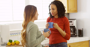 African American and Asian friends sipping coffee in kitchen stock photography