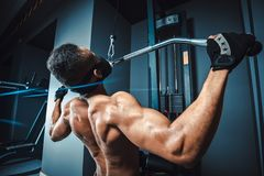 African american athletic man doing exercise in pull down machine back view. black fitness man working out lat pulldown training a. T gym Royalty Free Stock Photos