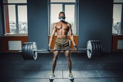 African american athletic man in sport mask doing deadlift with heavy barbell. black man lifting barbell opposite window. emotiona stock photo