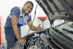 African-American Auto Tech Gives Thumbs Up. An automobile tech gives a thumbs up after looking under the hood Royalty Free Stock Photo