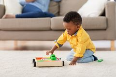 African american baby boy playing with toy blocks. Childhood, kids and people concept - lovely african american baby boy playing with wooden toy blocks kit on stock photo