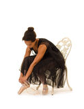 African American Ballerina Prepares for Class. An African American Ballerina Prepairs Pointe Shoes for Dance Class stock images