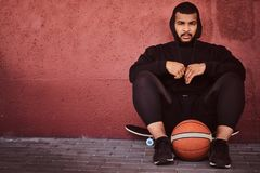 African-American bearded guy dressed in a black hoodie and sports shorts sitting on a skateboard with basketball and. Leaning on wall Royalty Free Stock Images
