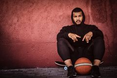 African-American bearded guy dressed in a black hoodie and sports shorts sitting on a skateboard with basketball and. Leaning on wall Royalty Free Stock Photos