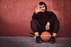 African-American bearded guy dressed in a black hoodie and sports shorts sitting on a skateboard with basketball and. Leaning on wall Stock Photos