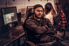 African-American bearded guy wearing hoodie and cap with her arms crossed sitting on a gamer chair in a gaming club or royalty free stock photography