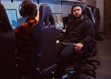 African American bearded guy wearing hoodie and cap sitting on a gamer chair and looking at a camera in a gaming club or. African-American bearded guy wearing stock photos