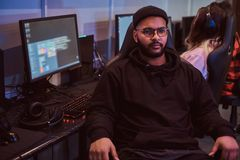 African American bearded guy wearing hoodie and cap sitting on a gamer chair and looking at a camera in a gaming club or. African-American bearded guy wearing royalty free stock images