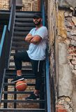 African-American bearded streetball player in cap dressed in a sportswear holds a basketball standing with crossed arms. On stairs in a ghetto Stock Photography
