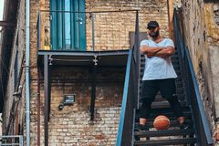 African-American bearded streetball player in cap dressed in a sportswear holds a basketball standing with crossed arms. On stairs in a ghetto Royalty Free Stock Photography