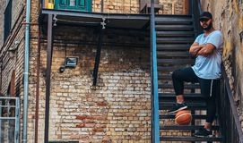 African-American bearded streetball player in cap dressed in a sportswear holds a basketball standing with crossed arms. On stairs in a ghetto Royalty Free Stock Photo