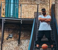 African-American bearded streetball player in cap dressed in a sportswear holds a basketball standing with crossed arms. On stairs in a ghetto Royalty Free Stock Images