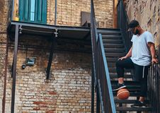 African-American bearded streetball player in cap dressed in a sportswear holds a basketball standing on stairs holds. Leg on a ball in a ghetto Royalty Free Stock Image