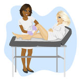 African american beautician waxing young blonde woman legs lying on spa bed Stock Photography