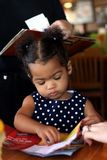 African-American, Bi-Racial Toddler Female. Little girl playing with coloring book at a restaurant with waitress in blurred background Royalty Free Stock Photos