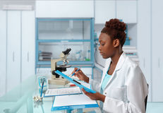 African-american biologist checks records in scientific lab or r. Esearch facility. Focus on the face and eyelashes Stock Images