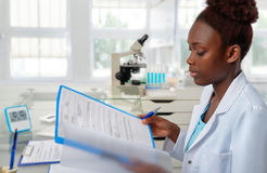African-american biologist checks records in scientific lab or r Stock Image