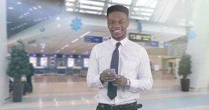 African American black man in a white shirt reading the message on a mobile phone. Young afro businessman keeps a smartphone in his hands and waits for the stock footage