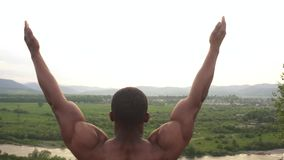 African american body builder with perfect body stretching on the mountain peak during his morning outdoor training. Sunrise sky background. Sport healthy stock video
