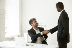 African-american boss congratulating caucasian employee with pro