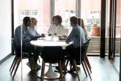 African American boss holding briefing with employees in boardroom. African American boss with employees sitting at desk in boardroom, businesswoman with stock photo