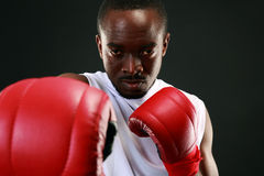 African American boxer punching in camera Stock Photo