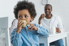 african american boy biting apple royalty free stock photo