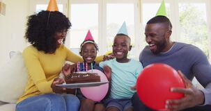 African american boy blowing candles on the cake and celebrating birthday with family at home
