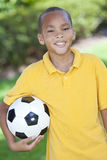 African American Boy Child & Football Soccer Ball. A young African American boy child outside playing holding soccer or football Royalty Free Stock Photo
