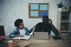 African American boy distracts father from work. When does homework at home. Child education concept. Fatherhood royalty free stock photos