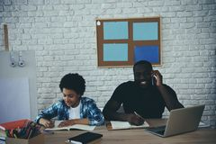 African American boy doing homework when father. Businessman working close by. Child education concept. Fatherhood royalty free stock photography