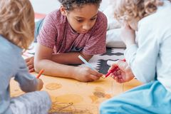 African-american boy drawing with classmate. African-american boy drawing with his classmate during art classes in preschool royalty free stock images
