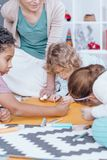 African-american boy drawing with kids. African-american boy drawing on paper with other kids sitting on the carpet at school Stock Images