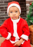 African American boy dressed costume Santa Claus by fireplace. Royalty Free Stock Photos