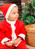 African American boy dressed costume Santa Claus by fireplace. Stock Photography