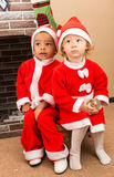 African American boy and girl dressed costume Santa Claus by fireplace. Stock Images