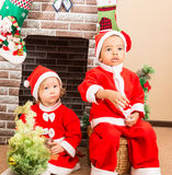 African American boy and girl dressed costume Santa Claus by fireplace. Christmas Stock Photo