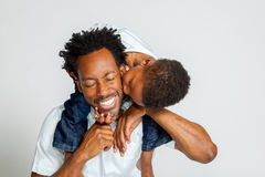 African American Boy Kisses Father. An African American boy on the shoulders of his father, leans over to kiss him on the cheek.  His father laughs with closed Royalty Free Stock Images