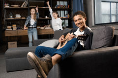 African american boy playing acustic guitar while girls dancing behind at home royalty free stock photo