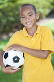 African American Boy Playing With Football. A young African American boy outside playing soccer or football on the grass in a park or garden Stock Photos