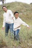 African-American boy pulling father on sand dunes. Happy African-American boy pulling father along sand dunes and grass at beach Royalty Free Stock Image