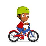 African american boy riding a bicycle. African american kid riding his bike with green protective helmet Stock Photo