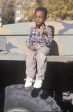 An African-American boy sitting on an U.S. army vehicle Stock Image