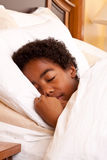 African American boy sleeping in his bed. Royalty Free Stock Images