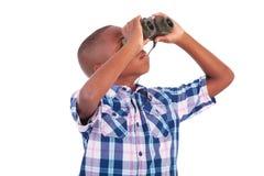 African American boy using binoculars - Black people. African American boy using binoculars, isolated on white background - Black people Royalty Free Stock Image