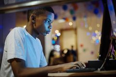 African american boy using a computer at night royalty free stock photos