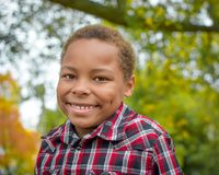 African American Boy. An African American boy  wearing a red and black checkered shirt with fall trees in the background Stock Photography