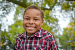 African American Boy with Dimples. An African American boy  wearing a red and black checkered shirt with fall trees in the background Royalty Free Stock Image