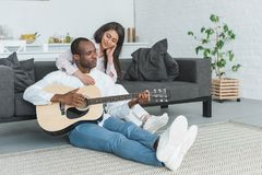 african american boyfriend sitting on floor and playing guitar for girlfriend stock images