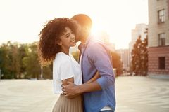 African-american boyfriend whispering words of love to girlfriend. Dating in the city royalty free stock photos